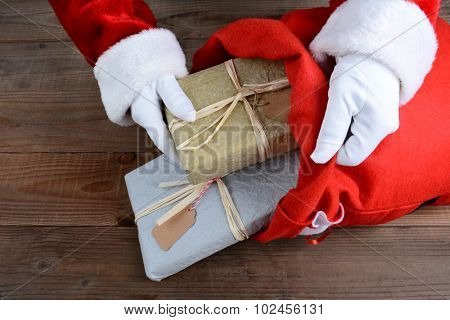 Closeup of Santa Claus putting packages in his bag on Christmas Eve.
