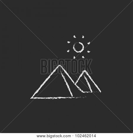 Egyptian pyramids hand drawn in chalk on a blackboard vector white icon isolated on a black background.