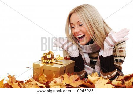 Woman with gift laying on dry autumn leaves isolated on white