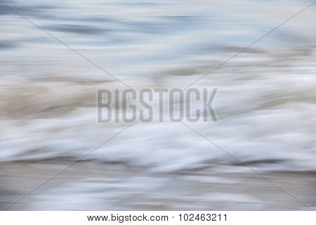 Ocean waves crashing on sandy beach abstract, in-camera motion blur.