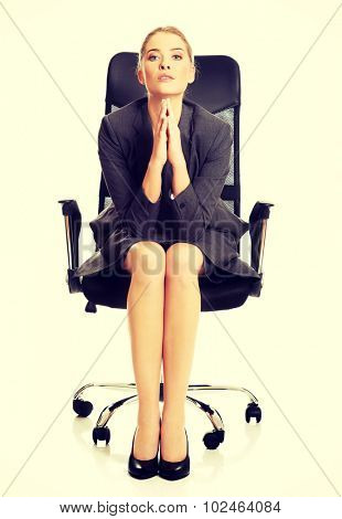 Sitting businesswoman with hands on chin.