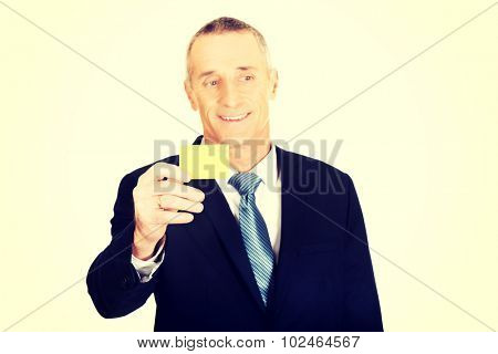 Mature businessman showing a yellow identity name card.