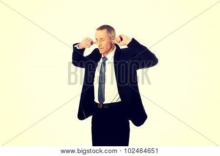 Mature businessman plugging his ears.