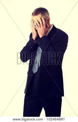 Stressed businessman covering his face with hands.