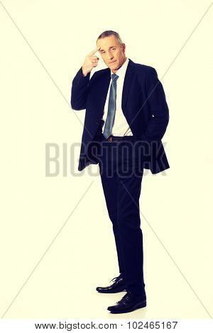 Full length businessman gesturing with finger against temple