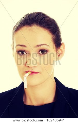 Beautiful businesswoman with broke cigarette in mouth.