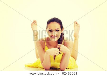 Beautiful woman lying on belly in yellow summer dress.