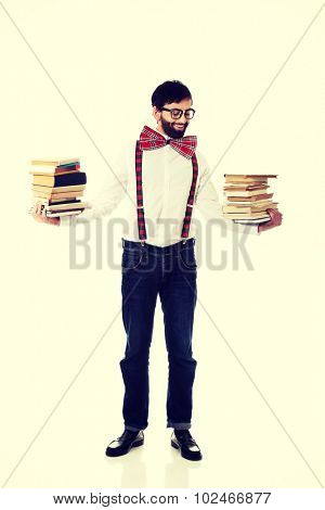 Handsome man wearing suspenders holding stack of books.