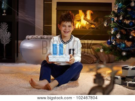 Happy boy smiling, holding christmas present, sitting on floor by christmas tree.