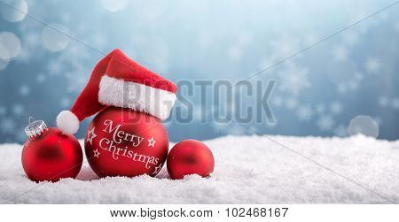 Christmas balls in the hat of Santa Claus on snow.