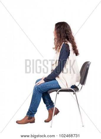 back view of young beautiful  woman sitting on chair.  girl  watching. Rear view people collection.  backside view of person.  A girl in a white tank top sitting on a stool and looking to the right.