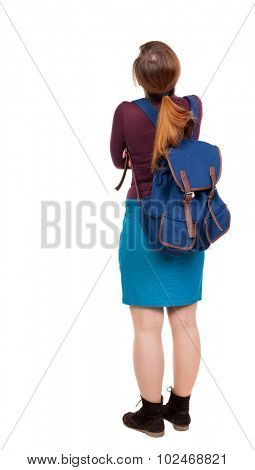 Back view of  woman with backpack looking up. Standing young girl. Rear view people collection.   girl in a blue skirt and a burgundy sweater with a blue backpack standing arms folded looking up.