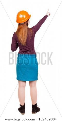 Back view of  pointing young women in helmet. Young girl gesture. Rear view people collection.  backside view of person.  Isolated over white background. Red-haired woman builder gives teams.