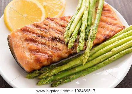 Grilled Salmon With Lemon, Asparagus On The Wooden Background