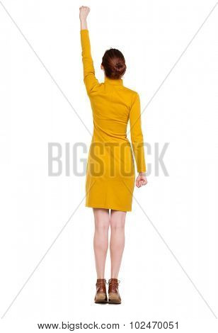 Back view woman. Raised his fist up in victory sign.  Rear view people collection.  backside view person.  Isolated over white background. Girl in a mustard-colored dress standing in a pose superhero