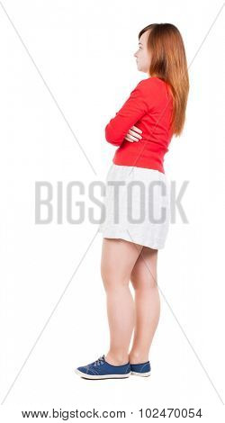 side  view of standing young beautiful  woman in dress. girl  watching. Rear view people collection.  Isolated over white background. Girl in white skirt standing sideways and looking to the right.