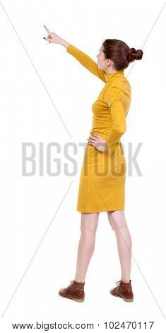 Back view of  pointing woman. beautiful girl. Rear view people collection.  Isolated over white background. Girl in mustard strict dress stands sideways resting his hand into the belt and shows up.