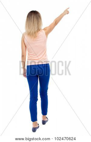 Back view of  pointing woman. beautiful girl. Rear view people collection.  backside view of person.  Isolated over white background. Blonde in blue pants and a pink blouse is pointing.