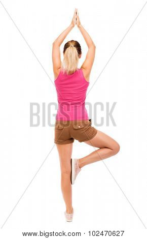 Back view girl standing in front of a warm up exercise.  Rear view people collection.  backside view of person.  Isolated over white background. The girl in brown shorts and a pink t-shirt doing yoga.