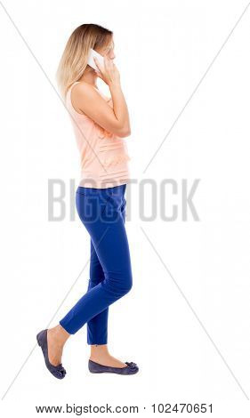 side view a woman walking with a mobile phone. beautiful curly girl in motion.    Rear view people collection. Isolated over white background.  Blonde in blue pants and a pink blouse is right on phone