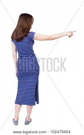Back view of  pointing woman. beautiful girl. Rear view people collection.  backside view of person.  Isolated over white background. A girl in a long blue dress she saw something left.