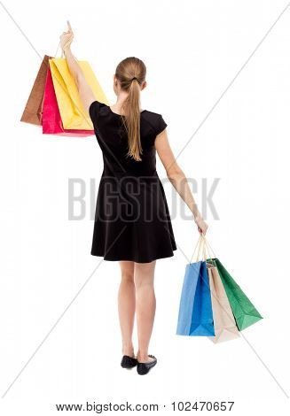 back view of woman  with shopping bags pointing . beautiful blonde girl in dress in motion.  backside view of person.  Rear view people collection. Isolated over white background.