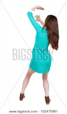 back view woman in dress protects hands from what is falling from above. Rear view people collection.  backside view person. girl in dress with brown boots closes her face against danger from above