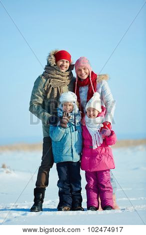 Happy family of four in winterwear looking at camera outdoors
