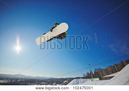 Sportsman on snowboard hanging over snowdrift
