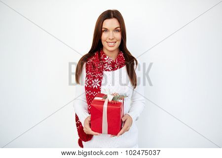 Happy girl in sweater and scarf holding giftbox