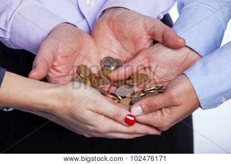 Group of people hands holding a lot of coins (selective focus)