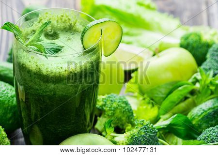 Fresh green vegetables and green smoothie with spinach in glass. Detox, diet or healthy food concept