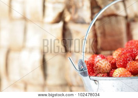 Bucket full of strawberries on wood birch bark background