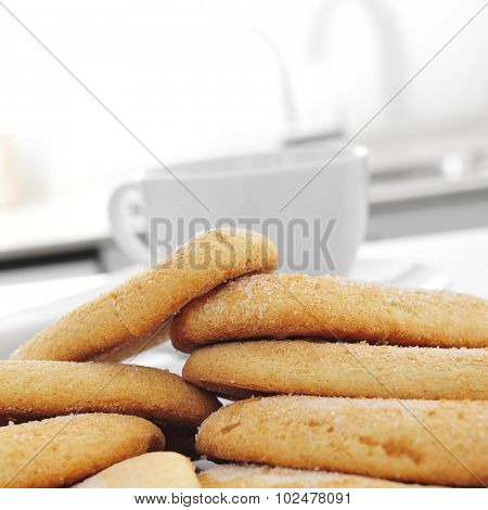 closeup of some ladyfingers and a cup of coffee or tea on the kitchen table