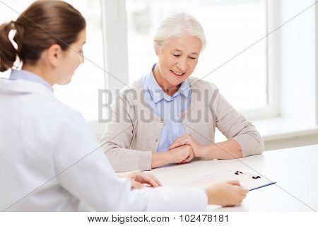 medicine, age, health care and people concept - doctor with clipboard and senior woman meeting at hospital