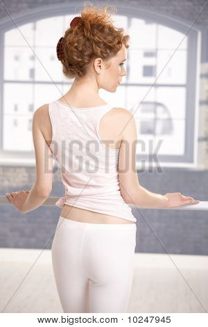 Young Girl Standing By Bar Showing Her Back