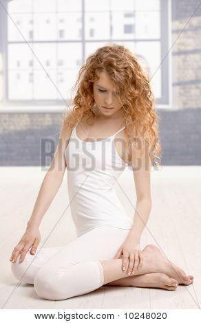 Attractive Female Sitting On Floor In Studio