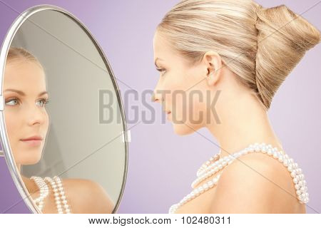 beauty, luxury, people, holidays and jewelry concept - beautiful woman with sea pearls beads or necklace looking to mirror over violet background