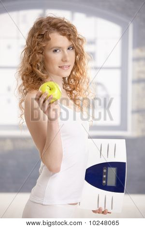 Pretty Female Holding Apple And Scale In Hands