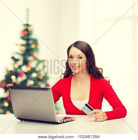 christmas, x-mas, electronics, gadget concept - smiling woman in red clothes with laptop computer and credit card