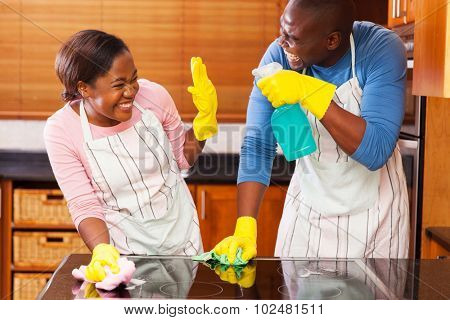 young african couple having fun while doing household chores