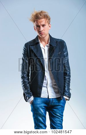serious young man looking at the camera while holding his hands in the pockets of his blue jeans