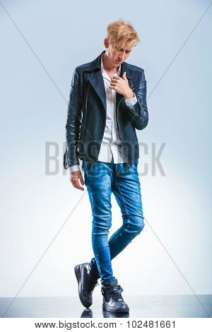 skinny young boy posing while looking down and holding his hand on the leather jacket