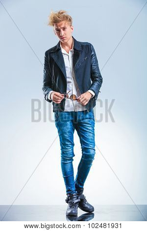 sexy blonde boy wearing jeans and leather jacket while holding sunglasses and looking forward