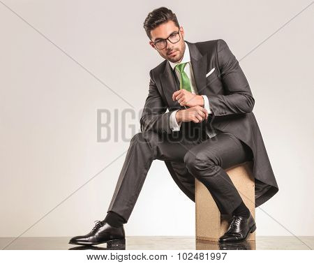 Side view of a elegant business man sitting on a wood box while fixing his sleeve.