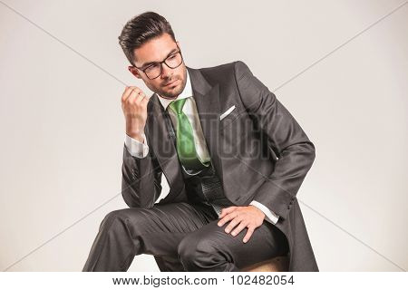 Attractive young business man looking down while sitting on a wood box.