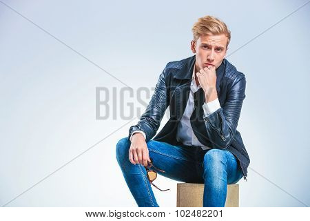 portrait of a young attractive man sitting on a box and thinking while touching his chin