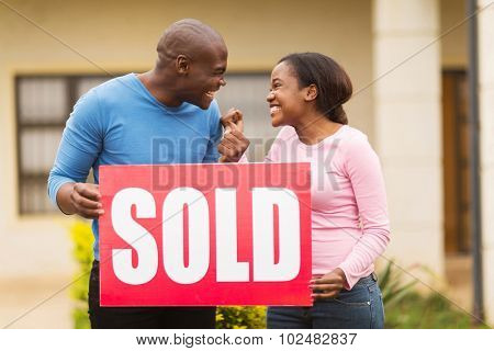 excited black couple holding sold sign outside their house