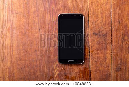 Smart phone on wooden table background with copy space
