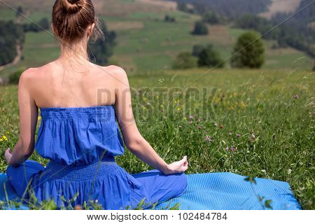 back of young girl in a meditation on the nature